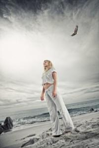 Woman on beach with gray sky